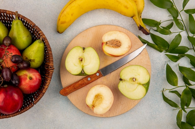 Top view of fruits as half cut peach and apple with knife on cutting board and basket of pear grape peach with banana and leaves on white background