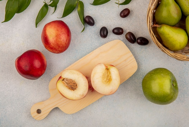 Top view of fruits as half cut peach on cutting board and bowl of pear with grape berries apple with leaves on white background