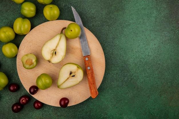 Vista dall'alto di frutta tagliata a metà pera e prugna con coltello sul tagliere e ciliegie su sfondo verde con spazio di copia