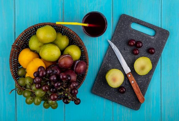Vista dall'alto di frutti come pluot tagliato a metà e acini d'uva con coltello sul tagliere e cesto di uva pluots e nettacot con bicchiere di succo d'uva su sfondo blu