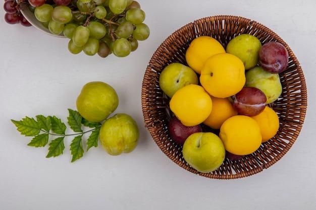 Vista dall'alto di frutti come nectacots pluots nel carrello con uva nella ciotola e pluots verdi su sfondo bianco