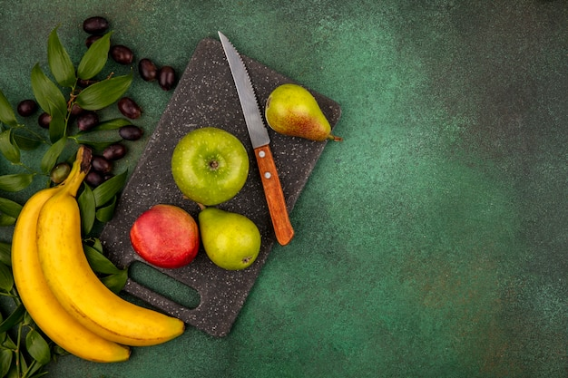 Top view of fruits as peach apple pear with knife on cutting board and grape banana with leaves on green background with copy space