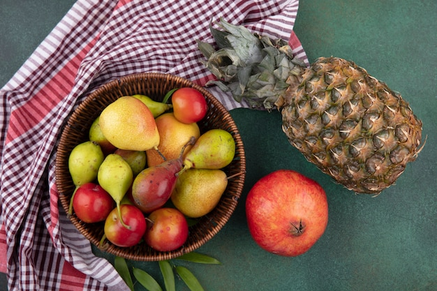 Top view of fruits as peach apple plum in basket on plaid cloth with pomegranate and pineapple on green surface