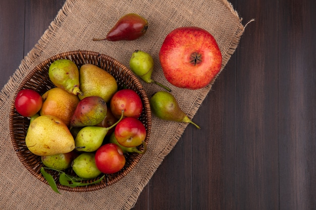 Top view of fruits as peach apple plum in basket with pomegranate on sackcloth on wooden surface