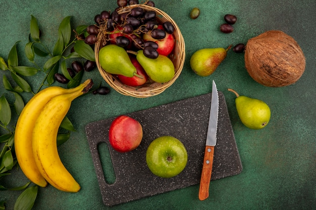Top view of fruits as peach apple with knife on cutting board and pear coconut grape banana with leaves on green background