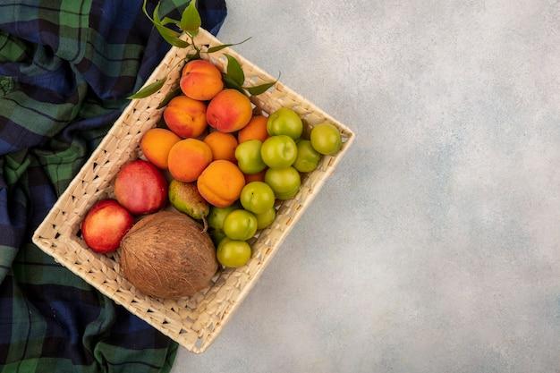 Vista dall'alto di frutti come pesca albicocca prugna noce di cocco nel cestello su plaid panno e sfondo bianco con copia spazio