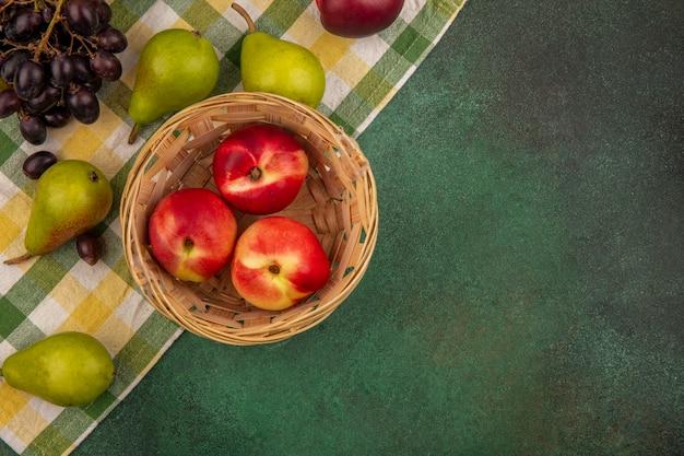 Vista dall'alto di frutta come pesca in cestino e uva pera su panno plaid su sfondo verde con spazio di copia