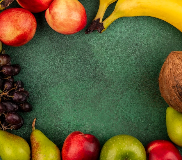 Top view of fruits as peach coconut apple pear banana grape on green background with copy space