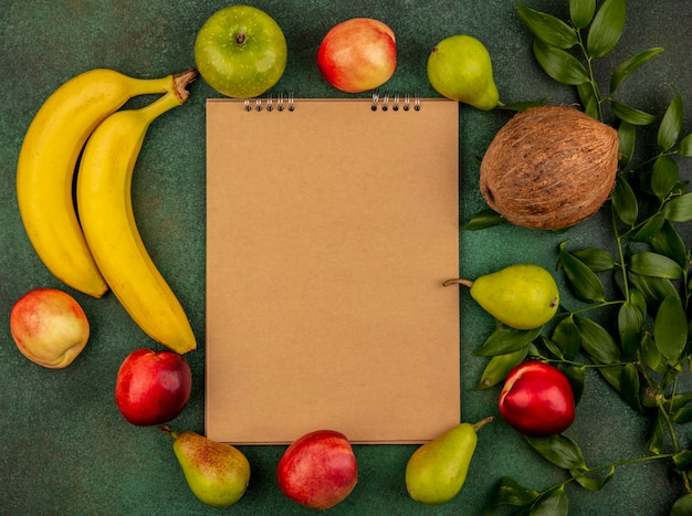 Top view of fruits as peach coconut apple pear banana with leaves around note pad on green background with copy space
