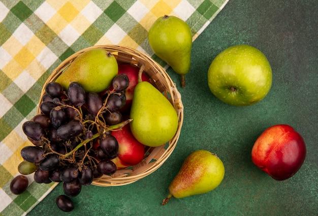 Vista dall'alto di frutta come uva da pesca e pera nel carrello su un panno plaid con mela su sfondo verde