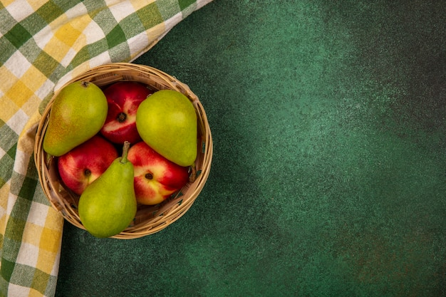 Top view of fruits as peach and pear in basket with plaid cloth on green background with copy space