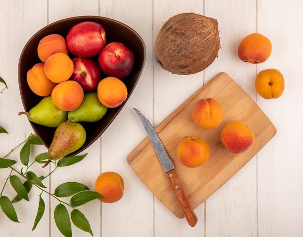 Vista dall'alto di frutti come pere pesche in una ciotola e pesche con coltello sul tagliere con cocco e foglie su fondo in legno