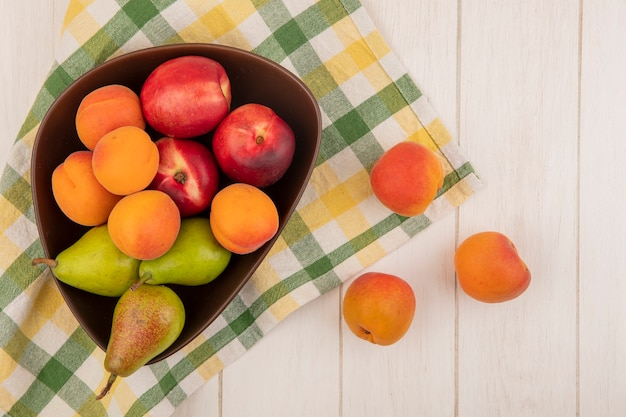 Vista dall'alto di frutta come pera pesca in una ciotola su un panno plaid e su sfondo di legno