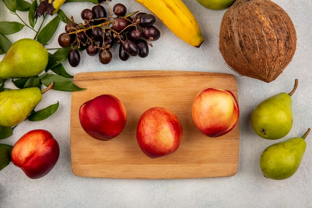 Top view of fruits as peaches on cutting board and grape pear coconut banana with leaves on white background