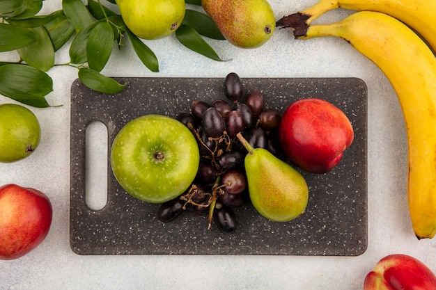 Top view of fruits as pear apple grape peach on cutting board with banana and leaves on white background