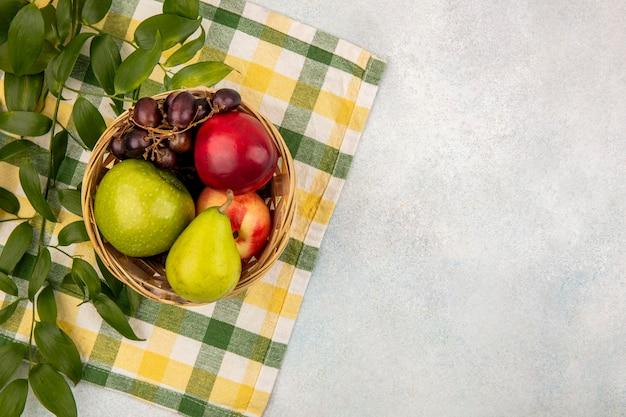 Vista dall'alto di frutti come pera mela pesca uva nel carrello con foglie su un panno plaid e sfondo bianco con spazio di copia