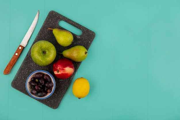 Top view of fruits as pear peach apple and grape berries on cutting board with lemon and knife on blue background with copy space