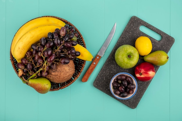 Top view of fruits as pear peach apple and grape berries lemon on cutting board and basket of banana coconut grape with knife on blue background