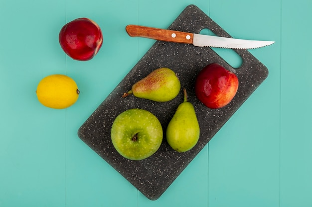 Top view of fruits as pear peach apple with knife on cutting board and lemon on blue background
