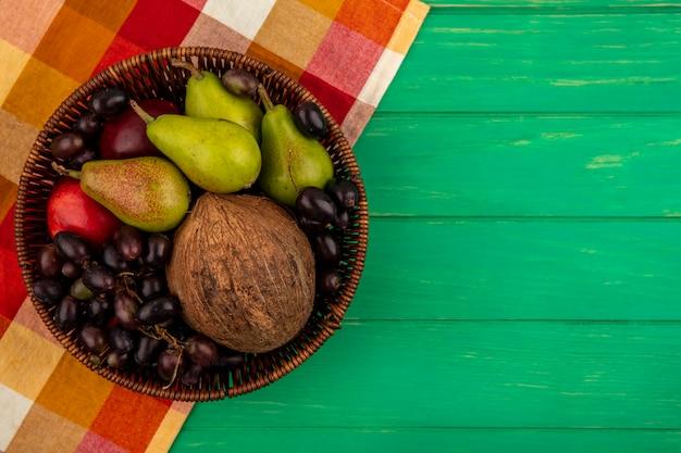 Vista dall'alto di frutti come pera pesca uva noce di cocco nel cestello su un panno plaid e sfondo verde con copia spazio