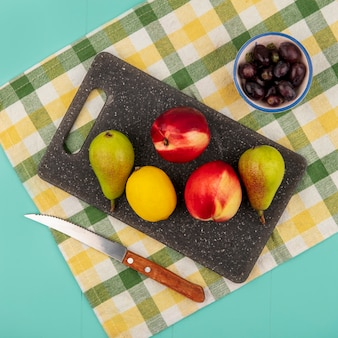 Top view of fruits as pear peach lemon on cutting board with grape berries and knife on plaid cloth on blue background