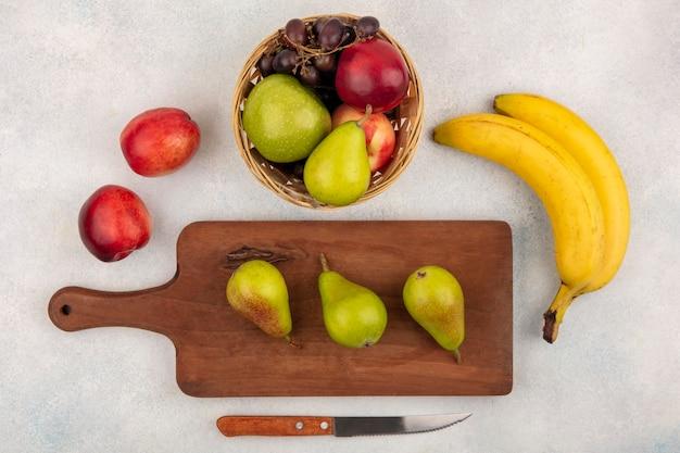 Vista dall'alto di frutta come pere sul tagliere e cesto di pesca uva mela pera con banane e coltello su sfondo bianco