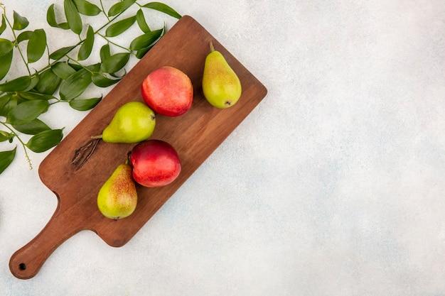 Vista dall'alto di frutti come pere e pesche sul tagliere con foglie su sfondo bianco con spazio di copia