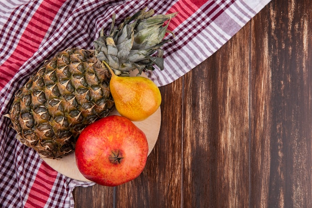 Top view of fruits as pineapple, pomegranate and peach on cutting board on plaid cloth and wooden surface