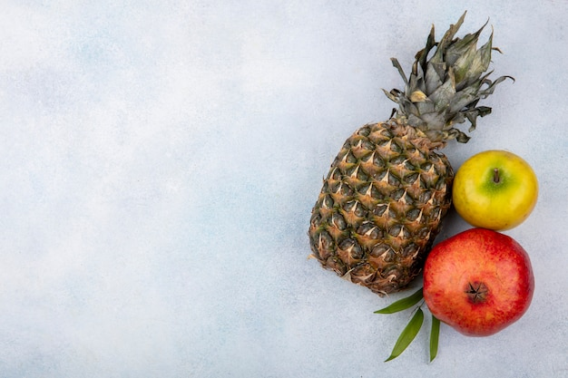 Top view of fruits as pineapple, pomegranate and peach on white surface with copy space