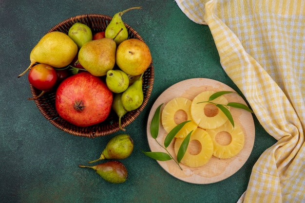 Top view of fruits as pineapple slices on cutting board with pomegranate peach plum in basket on green surface