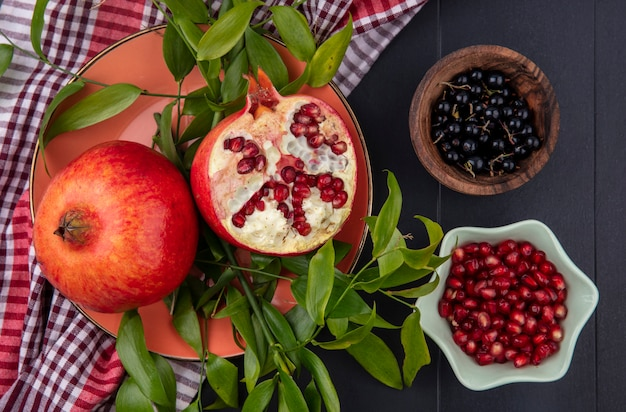 Top view of fruits as plate of pomegranate half and whole one with leaves on plaid cloth and bowls of sloe and pomegranate berries on black surface