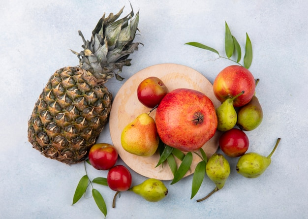 Top view of fruits as plum peach and pomegranate on cutting board and with apple and pineapple on white surface