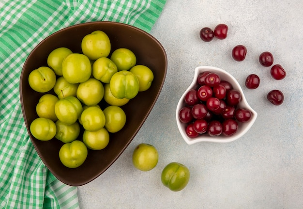 Top view of fruits as plums in bowl on plaid cloth and bowl of cherry on white background