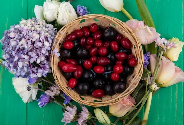 Vista dall'alto di frutti come prugnole e bacche di corniolo nel cesto con fiori intorno su sfondo verde