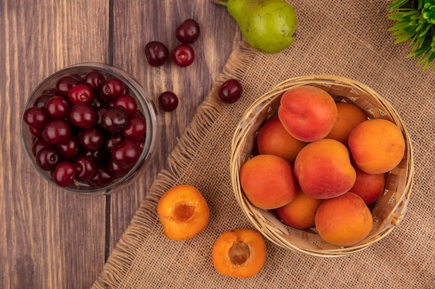 Top view of fruits as whole apricots in basket and half cut one on sackcloth with jar of cherries and pear on wooden background