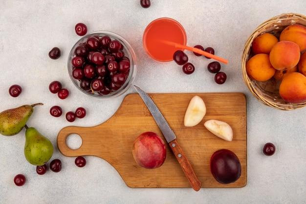 Vista dall'alto di frutta intera e pesche tagliate con coltello sul tagliere e succo di ciliegia con vaso di ciliegia e cesto di albicocca con pere su priorità bassa bianca