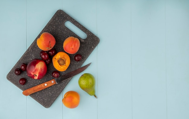Vista dall'alto di frutta intera e metà albicocche e pesche ciliegie con coltello sul tagliere e pera albicocca su sfondo blu con spazio di copia