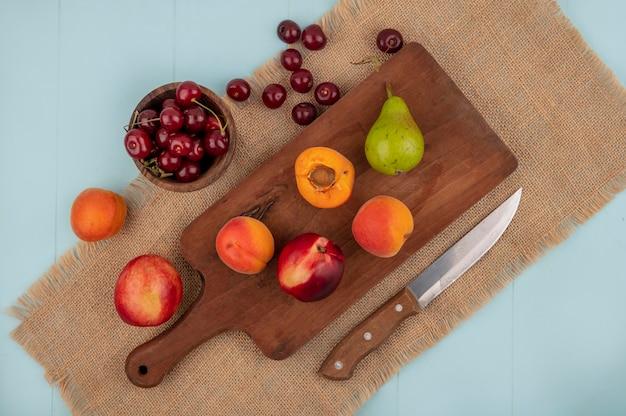 Vista dall'alto di frutta intera e metà albicocche e pere pesche sul tagliere e ciliegie nella ciotola e albicocche pesche con coltello su tela di sacco e sfondo blu