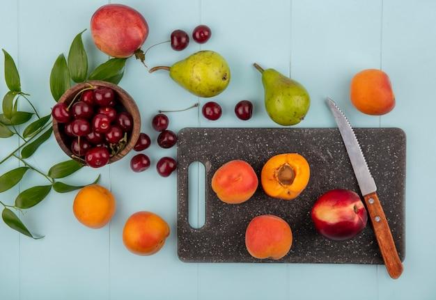 Vista dall'alto di frutta intera e metà albicocche e pesche con coltello sul tagliere e ciliegie nella ciotola e motivo di pera pesca albicocca ciliegia con foglie su sfondo blu