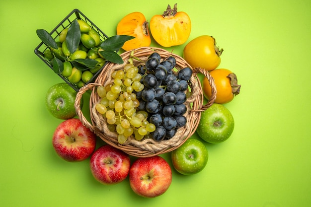 Vista dall'alto cesto di frutta di grappoli d'uva cachi mele cesto di agrumi