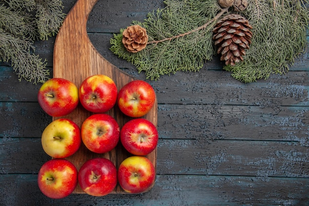 Top view fruits on board yellow-reddish apples on a cutting board on grey surface and tree branches with cones