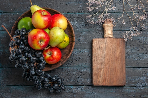 Top view fruits in bowl bowl of grapes pears apples limes next to branches and cutting board on dark table