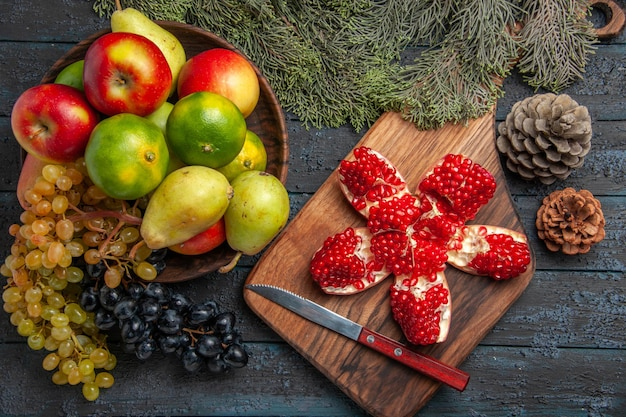 Top view fruits and branches white and black grapes limes pears apples in bowl next to pilled pomegranate knife on kitchen board and spruce branches with cones on dark table