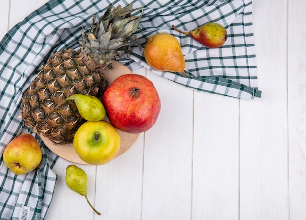 Top view of fruits on cutting board on plaid cloth with peaches on wooden surface with copy space