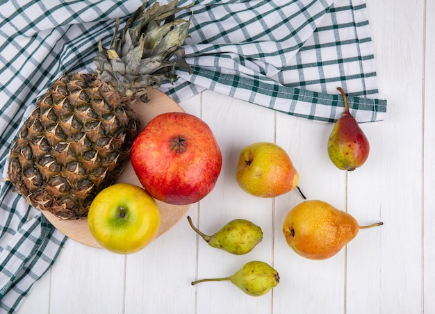 Top view of fruits on cutting board on plaid cloth with peaches on wooden surface