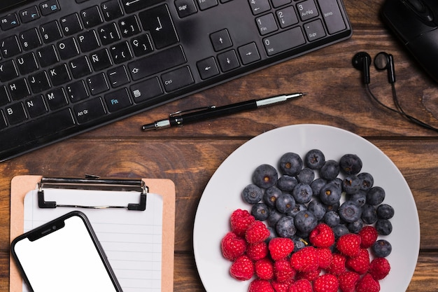 Top view fruits on plate and keyboard with blank notebook and phone