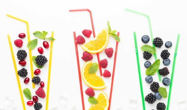 Top view of fruits in straw glasses with mint