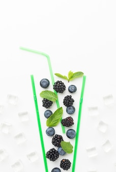 Top view of fruits in straws glass with copy space