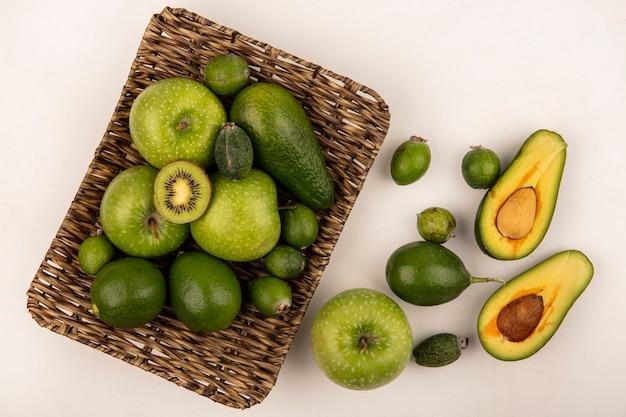 Vista dall'alto di frutti come mele verdi feijoas avocado su un vassoio di vimini con avocado feijoas e mela isolato su un muro bianco