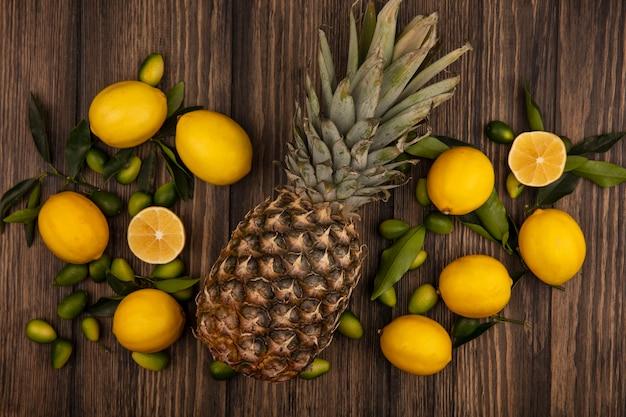 Vista dall'alto di frutti come ananas, limoni e kinkan isolati su una superficie di legno